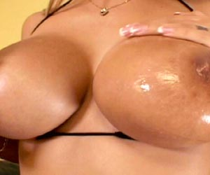 Busty Trina Michaels oiling up her massive tits